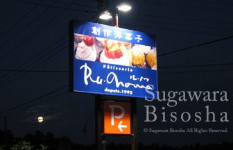 看板用照明が明るく照らす洋菓子店のポールサイン